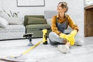Housewife with cleaning tools at home