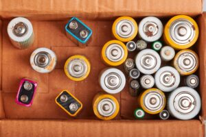 Discharged batteries in cardboard box. Collecting used batteries to recycle. Waste recycling