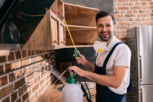 smiling pest control worker spraying pesticides on shelves in kitchen